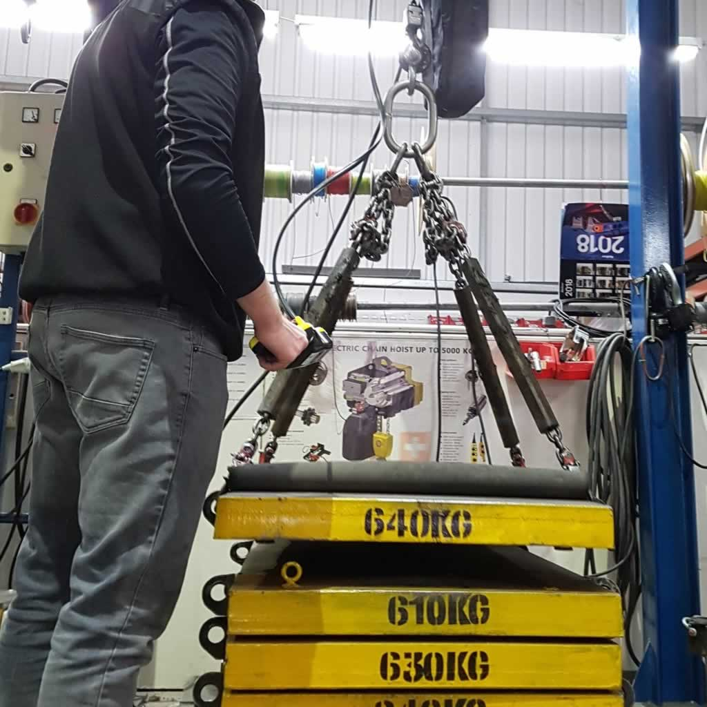engineer testing an electric chain hoist and chain slings
