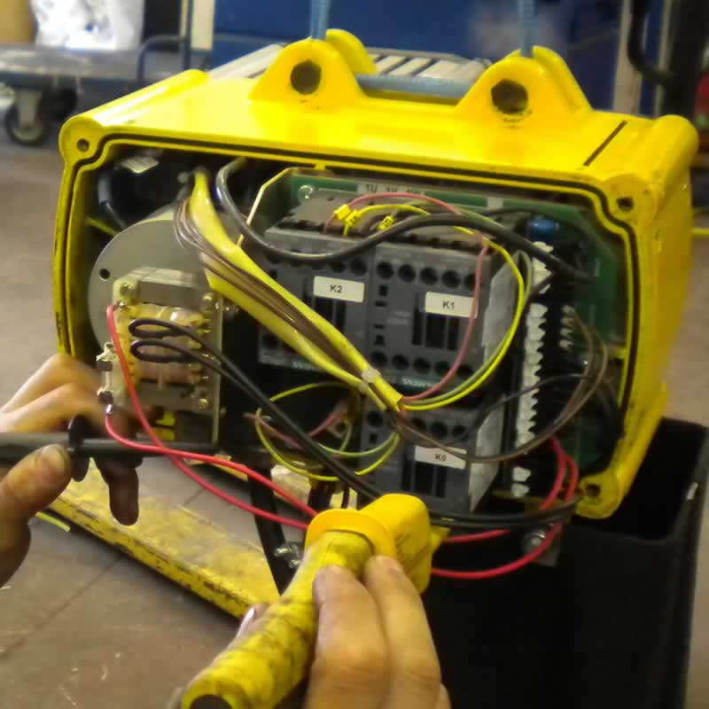 engineer performing a repair to an electric chain host in workshop