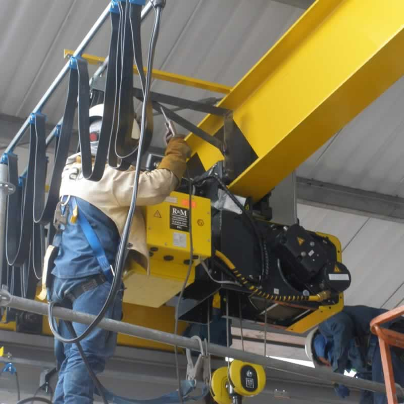 safety harnesssed engineer performing anelectric crane hoist inspectiion