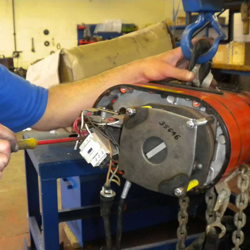 engineer repairing an electric chain hoist